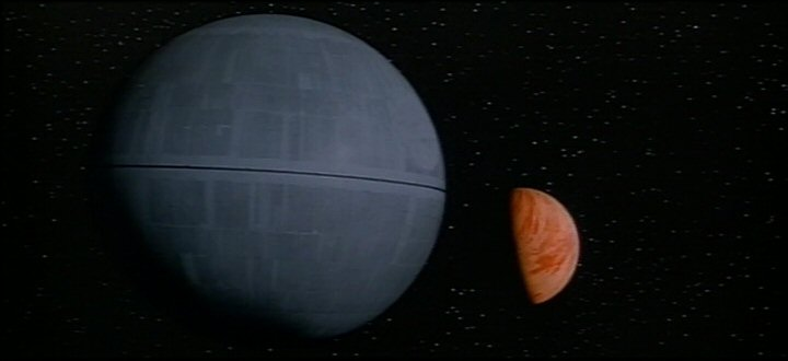 The Death Star arrives in the Yavin system and heads towards the planet.